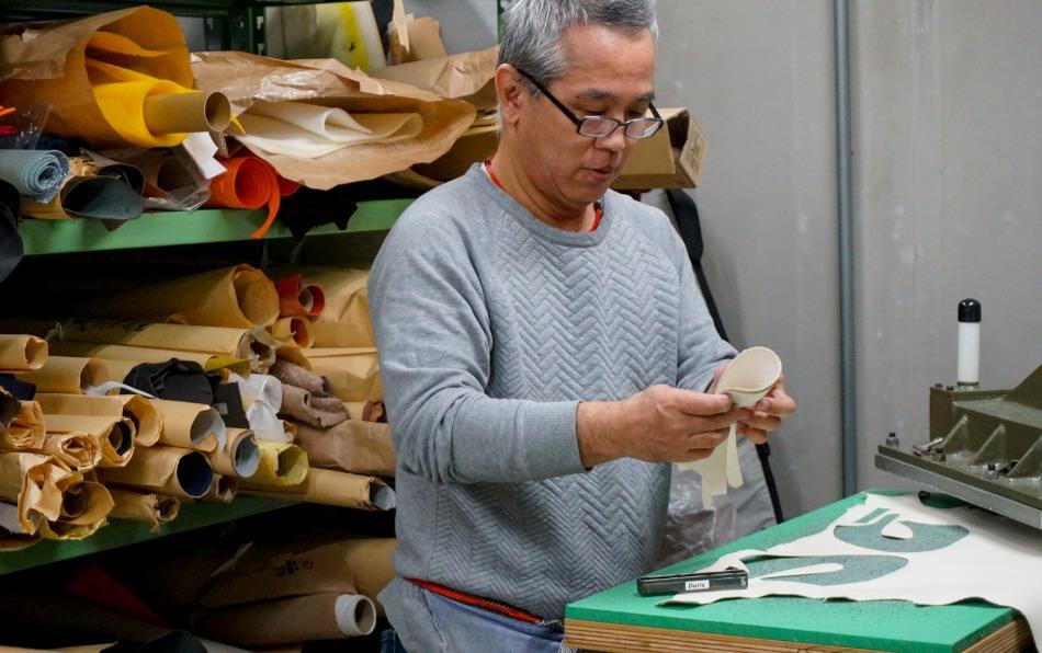 写真:金型を使って型抜きした革を手に取る倉本さん
