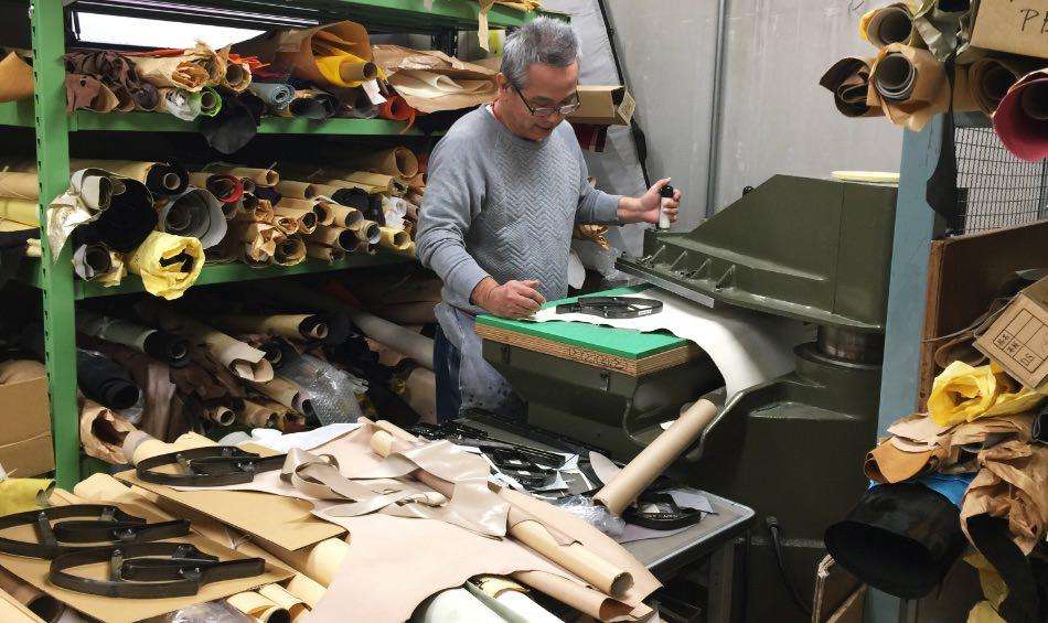 写真:革のたくさんおかれた作業場で実演してくれる倉本さん