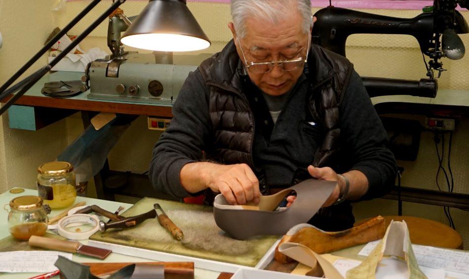 写真:作業机の上で、受け取ったパーツを手に取る安田 榮さん