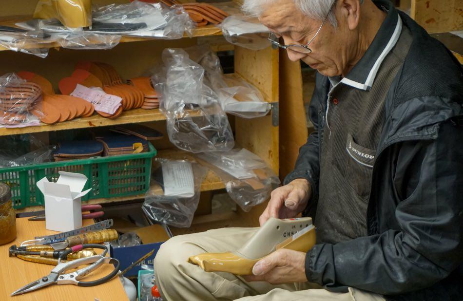 写真:甲革(アッパー)をかぶせた木型を手に持つ海老原さん