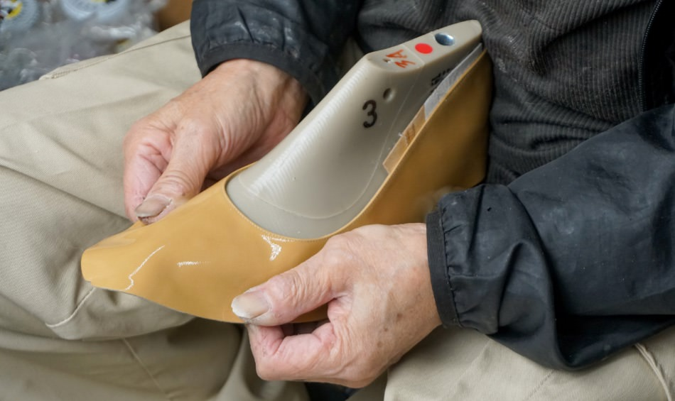 写真:木型に甲革をかぶせる海老原さん