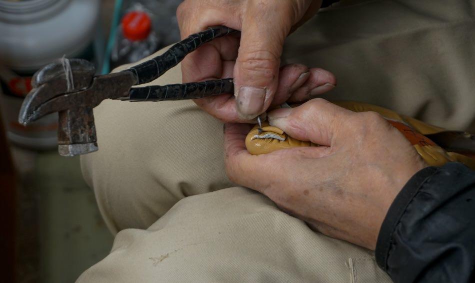 写真:つま先部分の甲革を中底に固定する様子