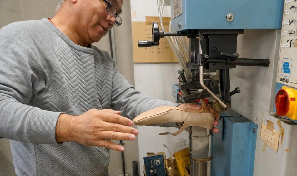 写真:ヒール付けの機械の前で底付けのシミュレーションをしてくれる倉本さん